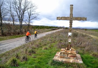 Two cyclists ride by wooden cross on Camino de Santiago in Spain.