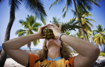 Cyclist eating a pineapple Hawaii Bike Tour