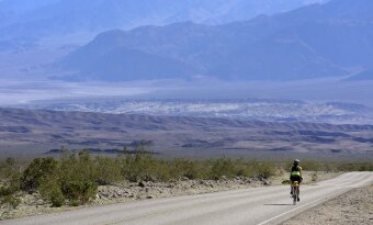 Cyclist biking in the desert Death Valley Bike Tour