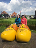 WomanTours pose four a photo with giant wooden clogs Holland Bike and Barge Meandering the Meuse Bike Tour