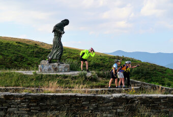 Cyclist posing with a statue Spain Camino de Santiago bike tour