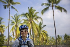 Cyclist posing for camera with coconut trees  Hawaii Bike Tour