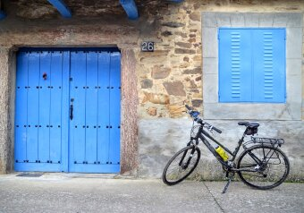 Bicycle in front of blue doors in small village on Camino de Santiago in Spain.