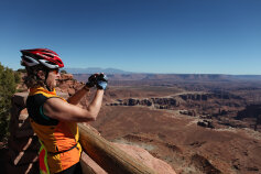 Cyclist taking a picture of scenery during Moab Arches and Canyonlands Bike Tour