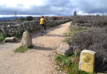 A cyclist rides a bike on an unpaved section of the Camino de Santiago in northern Spain.