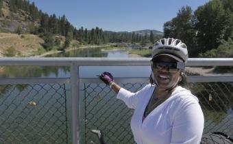 Cyclist posing for photon on bridge Idaho Greenways Bike Tour