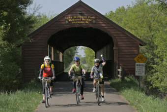 Cyclist under scenic bridge Minnesota Lake Wobegon Trail Bike Tour