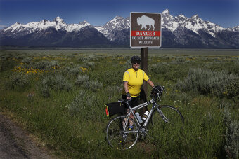 Cyclist posing for a photo by a buffalo sign Idaho Teton Valley Bike Tour