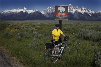 Cyclist posing for a photo by a buffalo sign Idaho Teton Valley Bike Tour