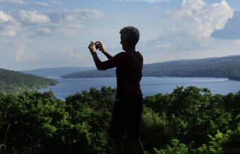 WomanTours guest taking a photo on the view Finger Lakes Bike Tour