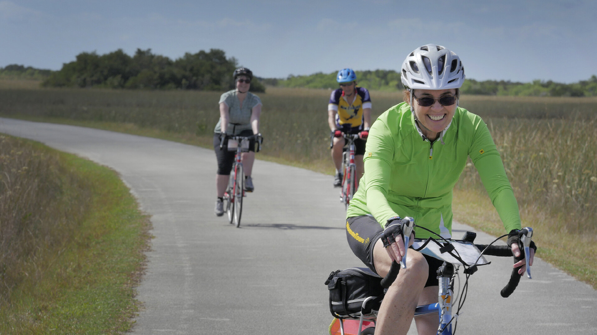Three women ride bikes on a bicycle path in Everglades National Park on our Florida bike tour.