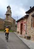 Cyclist rides bike in small village on the Camino de Santiago in Spain.