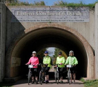 Four WomanTours cyclists celebrate their climb to the Great Continental Divide on the Great Allegheny Passage.