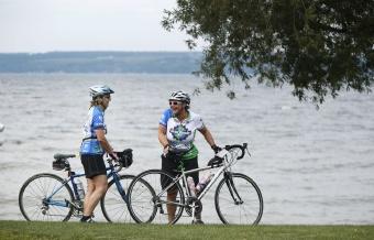 Cyclist resting by lake shore Finger Lakes Bike Tour