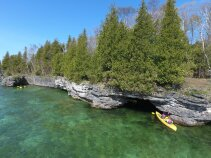 Exploring a cave while kayaking on our Wisconsin Door County bike tour.